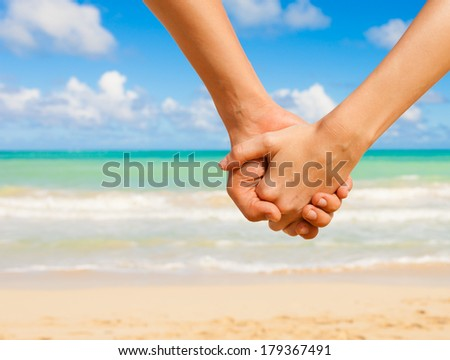 Happy couple holding hands on the beach in Hawaii.