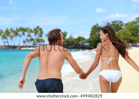 Happy couple holding hands running having fun playful on the beach. Young people from behind playing together on summer travel destination tropical holidays. Trust and relationship concept.