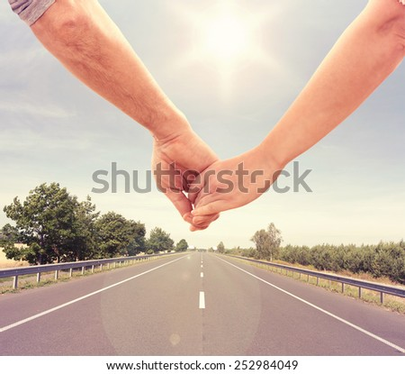 Happy couple holding hands together walking along road - stock photo