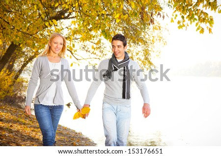 Happy couple holding hands under the leaves on the river bank - stock photo