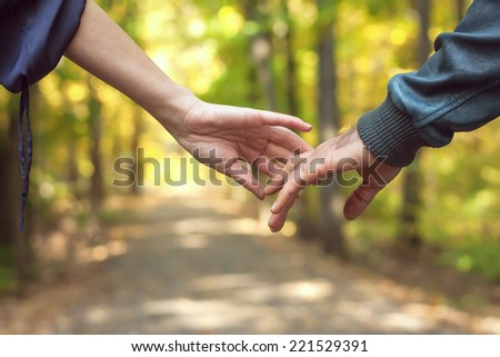 Happy couple holding hands when man and woman walk in the Park in autumn - stock photo