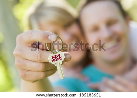Happy Couple Holding House Key with New Home Text On The Key. - stock photo