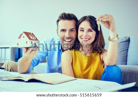 Happy couple holding key to new home
