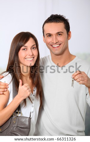 Happy couple holding keys of their new home - stock photo