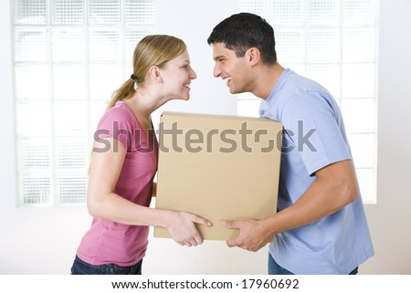 Happy couple holding one cardboard box. They're looking at each other. Side view. - stock photo