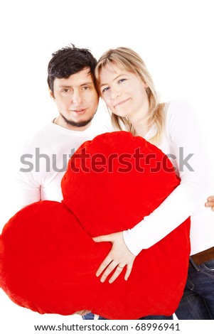 Happy couple holding red heart pillow over white background