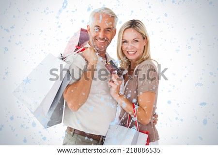 Happy couple holding shopping bags and credit card against snow falling - stock photo