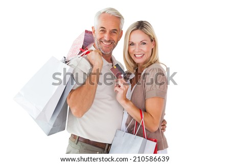 Happy couple holding shopping bags and credit card on white background - stock photo