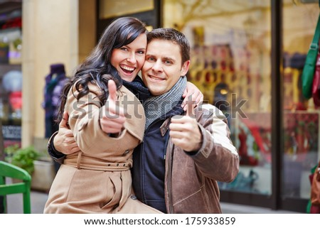 Happy couple holding their thumbs up while shopping in a city - stock photo