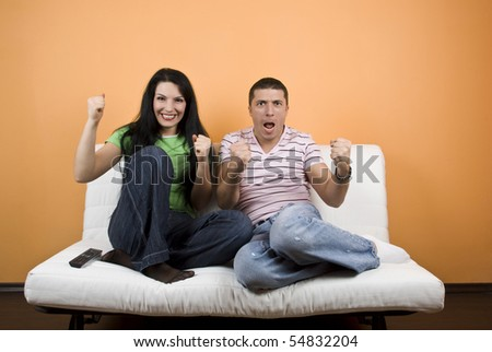 Happy couple home  watching TV their favorite sport team  or favorite match over television and they exclaim  gladly  :GOAL - stock photo