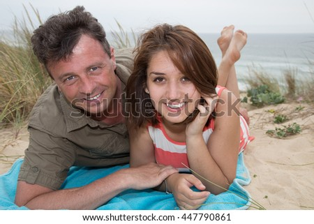 Happy couple hugging and laughing together at beach