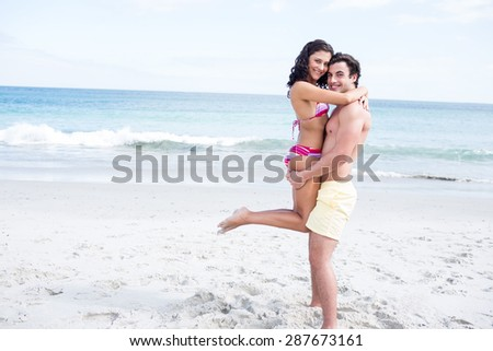 Happy couple hugging and looking at camera at the beach - stock photo