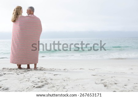 Happy couple hugging each other and looking at the sea with blanket around them at the beach - stock photo