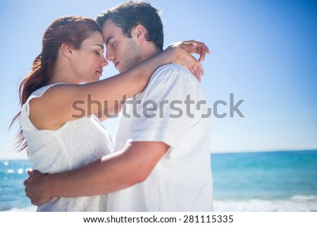 Happy couple hugging eyes closed at the beach