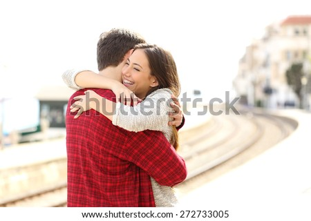 Happy couple hugging in a train station after arrival - stock photo