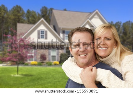 Happy Couple Hugging in Front of Beautiful House. - stock photo