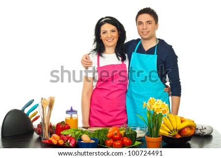 Happy couple hugging in their kitchen against white background