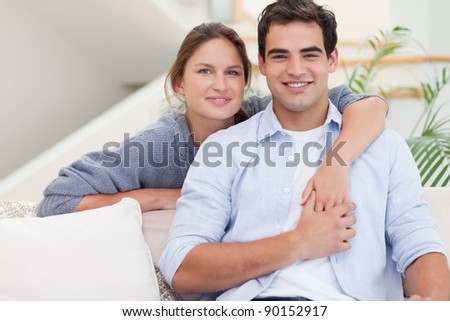 Happy couple hugging while looking at the camera - stock photo