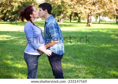 Happy couple - Husband and his pregnant wife kissing in autumn park - stock photo