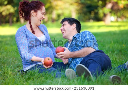 Happy couple - Husband and his pregnant wife relaxing in autumn park - stock photo