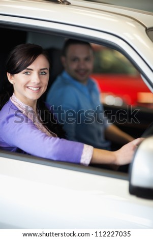 Happy couple in a car while smiling - stock photo