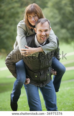 happy couple in a city park, man carrying woman on his back