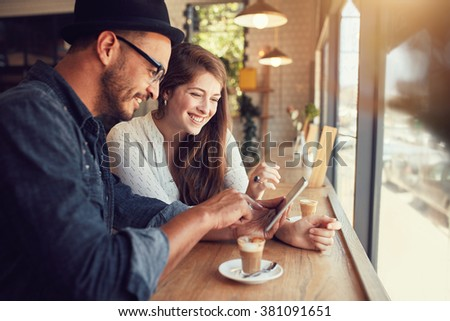 Happy couple in a coffee shop surfing internet on digital tablet. Young man and woman in a restaurant looking at touch screen computer. - stock photo