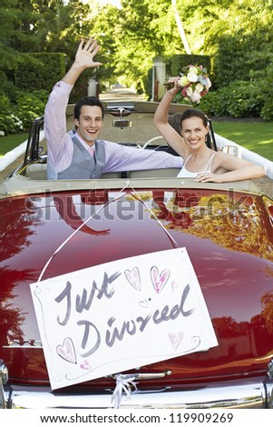 Happy couple in a convertible car waving with just divorced sign on it - stock photo