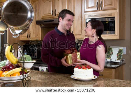 Happy couple in a kitchen smiling near a cake, fruit, pots and pans and a microwave. Both are holding a present while smiling at each other. Horizontally framed photograph.
