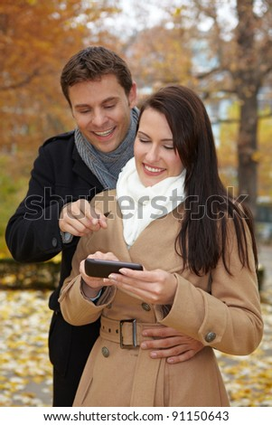 Happy couple in autumn using a smartphone - stock photo