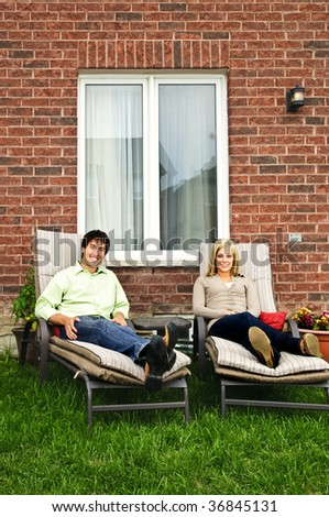 Happy couple in backyard of new home sitting on lounge chairs - stock photo