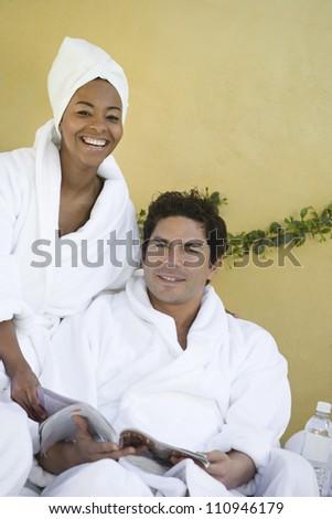 Happy couple in bathrobe reading magazine - stock photo