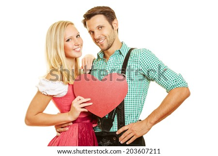 Happy couple in Bavaria in dirndl and leather pants with a red heart - stock photo