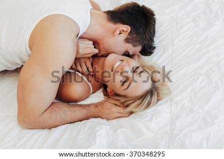 Happy couple in bedroom enjoying sensual foreplay - stock photo