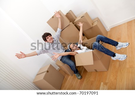 Happy couple in cardboard boxes moving to a new house