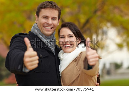 Happy couple in fall park holding their thumbs up - stock photo