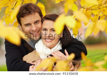 Happy couple in fall under leaves of a broad leaved lime - stock photo