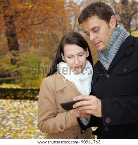 Happy couple in fall using mobile internet with smartphone - stock photo