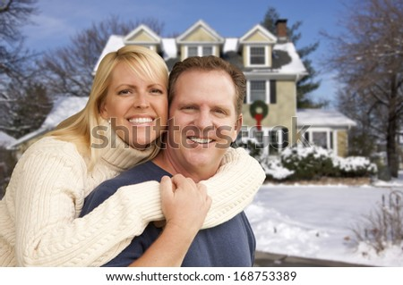 Happy Couple in Front of Beautiful House with Snow on the Ground. - stock photo