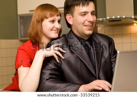 Happy couple in kitchen with laptop
