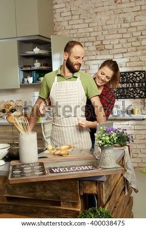 Happy couple in kitchen, woman tieing apron on man. - stock photo