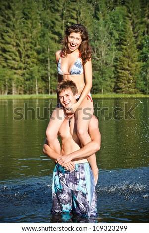 Happy couple in lake wearing swimwear - stock photo