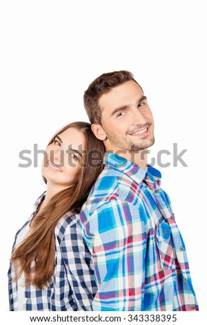 Happy couple in love holding hands standing back to back - stock photo