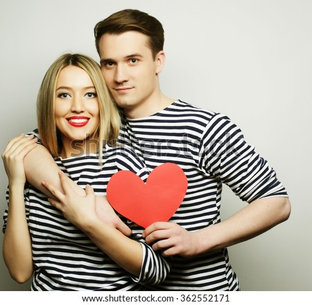 Happy couple in love holding red heart - stock photo