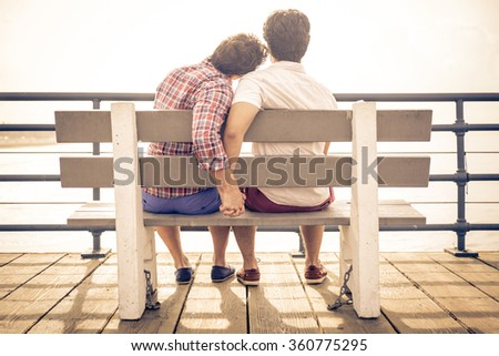 happy couple in love  in Santa monica sitting on a bench. People and relationship concept - stock photo