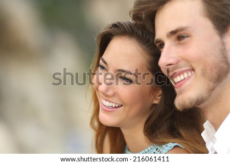 Happy couple in love looking away together with an unfocused background           - stock photo