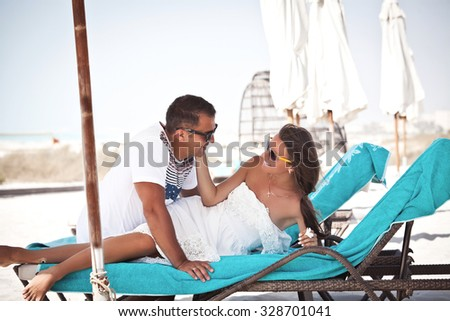 Happy couple in love on beach. Couple enjoying the perfect summer morning on tropical resort. Luxury vacation.