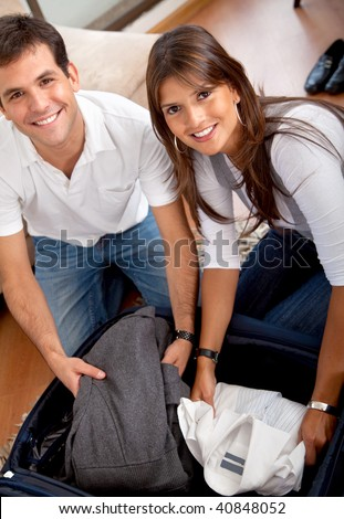Happy couple in love packing for their honeymoon