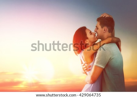 Happy couple in love. Stunning sensual portrait of young stylish fashion couple outdoors. Young man and woman on background sunset sky. - stock photo