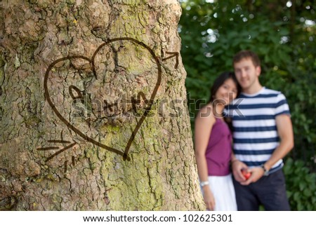 Happy couple in love with their initials carved in a tree - stock photo